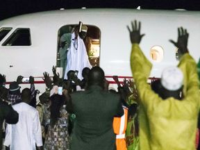 Former president Yaya Jammeh (C,up), the Gambia's leader for 22 years, waves from the plane as he leaves the country on 21 January 2017 in Banjul.