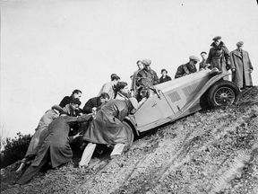 Group of men helping a competitor get up a steep hill in Surrey