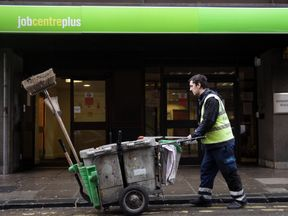 A street cleaner passes the Jobcentre Plus office on January 18, 2012 in Bath