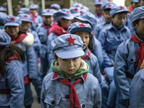 Children wearing uniforms wait to enter their classroom on January 21, 2015 at the Beichuan Red army elementary school in Beichuan