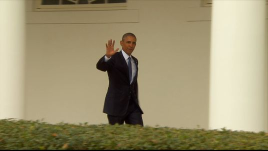 Barack Obama waves to the media at the White House