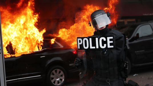 A limo is set on fire amid clashes between protesters and police officers