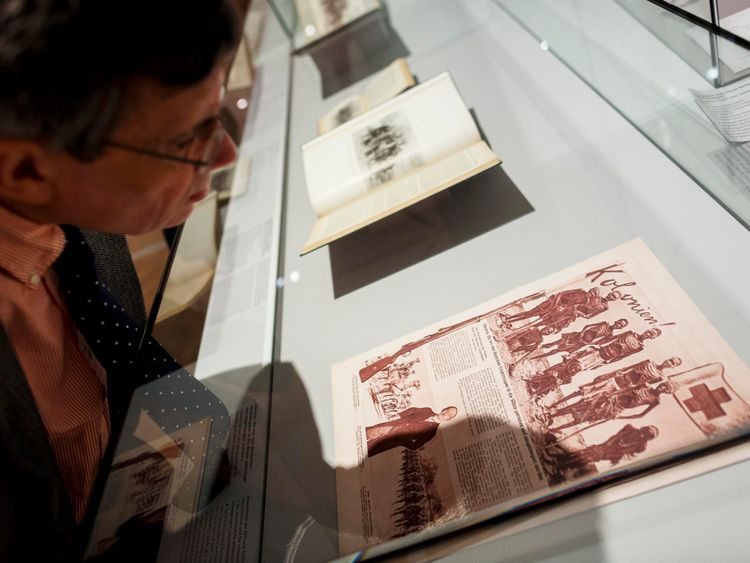 A visitor looks at documents related to the Herero Massacre during an exhibition