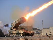 Iraqi army launch a rocket towards Islamic State militants near Ghozlani military complex, south of Mosul