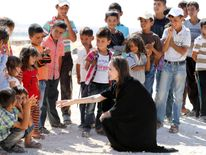 Jolie talks to children on a visit to a refugee camp
