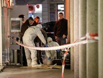 Police officers investigate a car in front of a business building in Heidelberg, western Germany, where a man ploughed into pedestrians