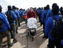A member of an Israeli settler family pushes a stroller past Israeli policemen