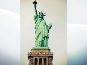 Activists hoist 'Refugees Welcome' sign at the Statue of Liberty in New York