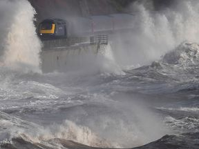 A train moving through the waves on the coastal railway in Devon