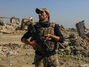 An Iraqi forces officer beside a destroyed Mosul airport building