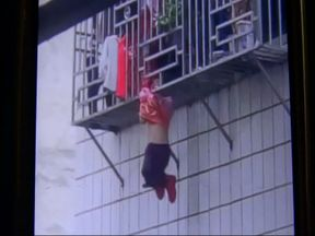 A girl seen hanging from a window grill in China