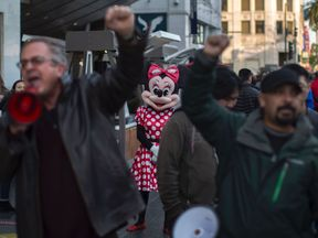 A Minnie Mouse character looks on as people protest at the Hollywood Walk of Fame star for Donald Trump in reaction to a Twitter post by US President-elect Trump referring to expansion of the United States nuclear arsenal on December 25 in Los Angeles, California.
