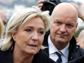 Marine Le Pen and, behind her, bodyguard Thierry Legier
