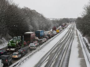 Traffic on the M80 near Falkirk during early morning snowfall, as flights have been cancelled and commuters were warned they faced delays after Storm Doris reached nearly 90mph on its way to batter Britain
