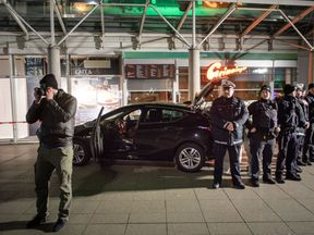 Police officers stand around a car in front of a business building in Heidelberg, where a man ploughed into pedestrians