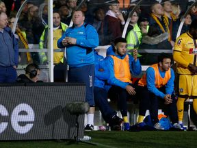 Sutton United's substitute Wayne Shaw eats a pie