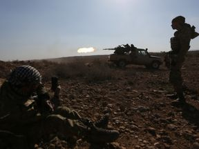 Rebel fighters fire their weapon during an offensive against Islamic State militants, on the outskirts of al-Bab