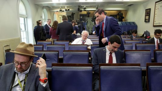 Glenn Thrush (L), chief White House political correspondent for the The New York Times, works in the briefing room after being excluded