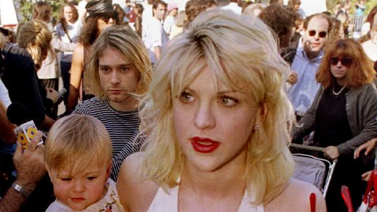 Kurt Cobain walks behind his wife Courtney Love and their daughter Frances Bean Cobain in LA in 1992