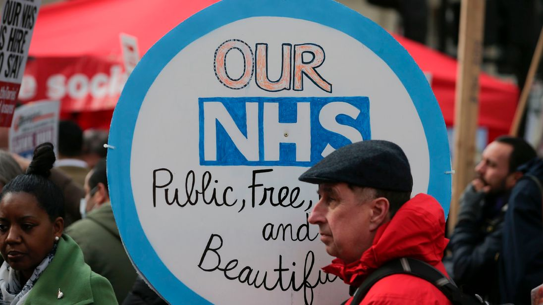 A protester holds a placard during a march against private companies' involvement in the National Health Service (NHS) and social care services provision and against cuts to NHS funding in central London on March 4, 2017. People gathered to demonstrate at the rally publicised by the People's Assembly Against Austerity to demand a fully and publicly funded NHS and social care service, returned fully to public ownership and provision and to say no to cuts in NHS funding