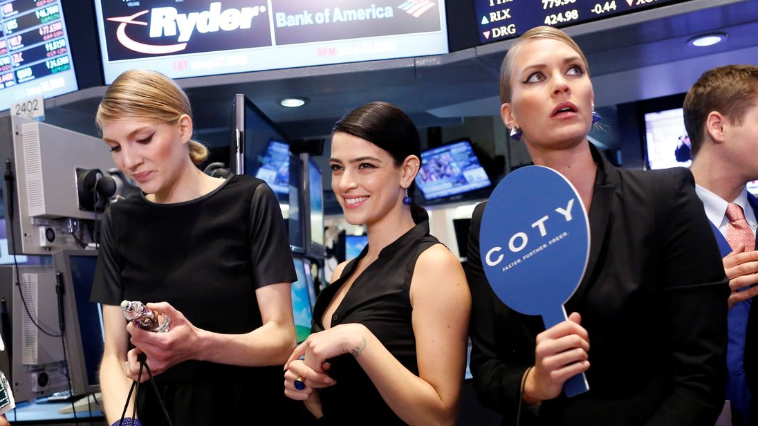 Models gather at a trading post on the floor of the New York Stock Exchange for the IPO of Coty Inc. June 2013