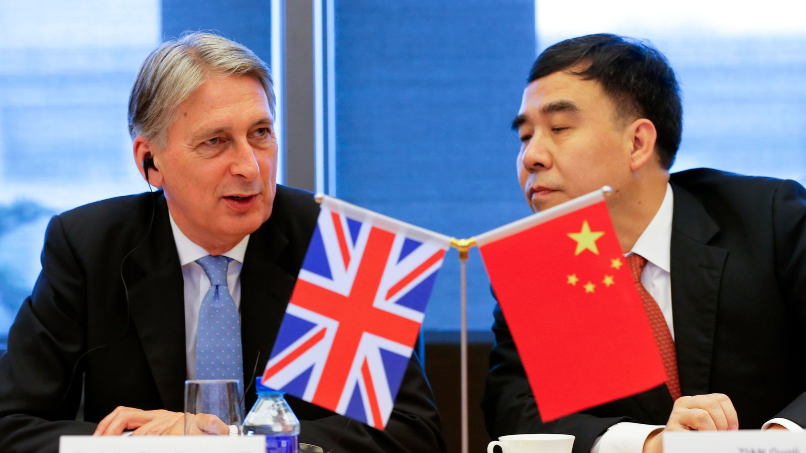 Close crop of flags as Chancellor Philip Hammond (L) and Bank of China chairman Tian Guoli (R) attend the UK-China High Level Financial Services Roundtable at the Bank of China head office building in Beijing on July 22, 2016.