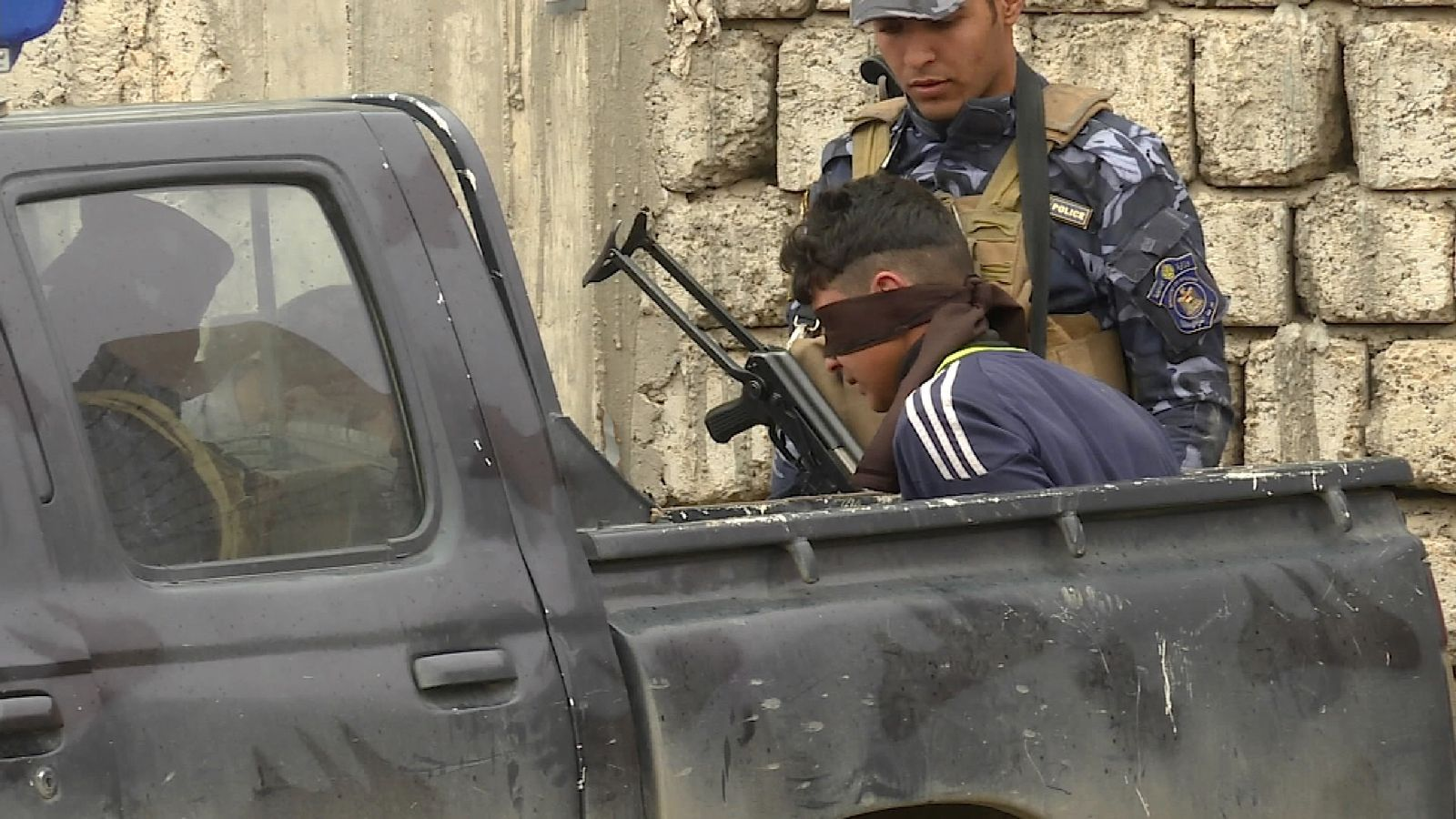 A suspected militant is blindfolded by Iraqi troops