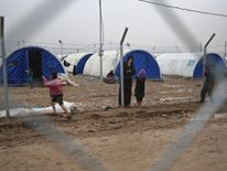 Displaced Iraqis stand near a fence at the Hamam al-Alil camp