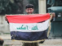 A member of the Iraqi forces raises a battered national flag on the outskirts of the old city