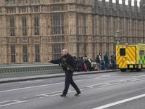 An armed police officer runs accross the road during an incident on Westminster Bridge