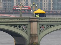 Police officers and forensics investigators work on Westminster Bridge