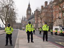 British police officers bow their heads as they stand near a police cordon