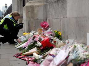 A police officer places a floral tribute near Westminster Bridge