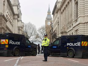 A police officer stands in front of armoured police personnel carriers on a street leading to the Houses of Parliament