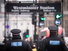 Police officers walk near Westminster Station in central London