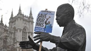 A poster hanging from the Statue of Nelson Mandela at a rally in central London, in support of the NHS