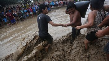 Residents cross a flooded street after a massive landslide and flood in Trujillo, northern Peru