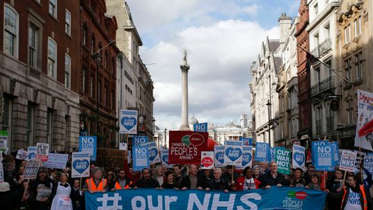 A group of protesters hold placards as others march through central London during a demonstration in support of the NHS on March 4, 2017 in London, England. Thousands march from Tavistock Square to Parliament today for a demonstration against hospital closures, privatisation and cuts to the NHS
