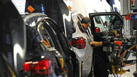 A Vauxhall employee works on a vehicle on the production line at the Vauxhall car factory in Ellesmere Port