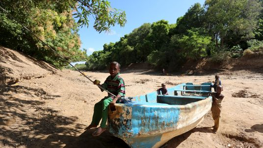 Children play on an abandoned boat along the Shabelle River bed, which is dry due to drought in Somalia's Shabelle region
