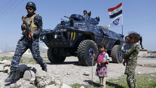 Displaced Iraqi children, who fled their homes in the Old City in western Mosul due to the ongoing fighting between government forces and Islamic State (IS) group fighters, are seen looking towards a security forces member ahead of being taken to the Hammam al-Alil camp, south of Mosul, on March 27, 2017
