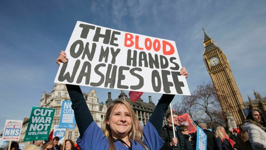A protester, an NHS doctor, holds a placard up in front of the Elizabeth Tower, also known as Big Ben at the Houses of Parliament during a march against private companies' involvement in the National Health Service (NHS) and social care services provision and against cuts to NHS funding in central London on March 4, 2017