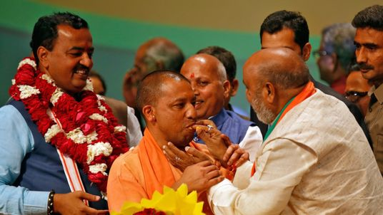 India's ruling Bharatiya Janata Party (BJP) leader Yogi Adityanath (C) is offered sweets after he was elected as Chief Minister of India's most populous state of Uttar Pradesh