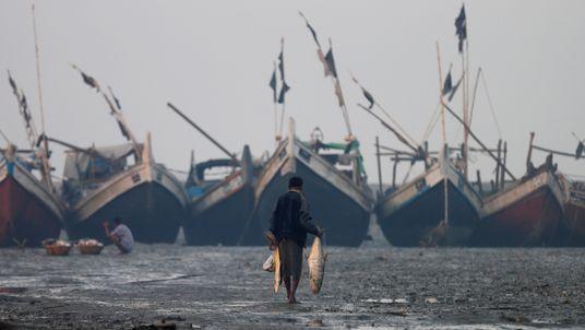 A Rohingya fisherman walks on the beach in Sittwe in the state of Rakhine, Myanmar
