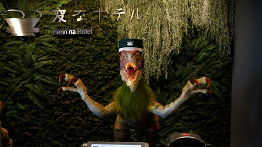 A dinosaur robot acting as a receptionist demonstrates how to check-in to the Henn na hotel in Urayasu, east of Tokyo