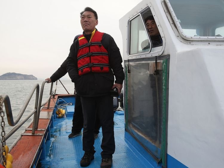 A relative of one of the victims of the sunken Sewol ferry watches the salvage operation