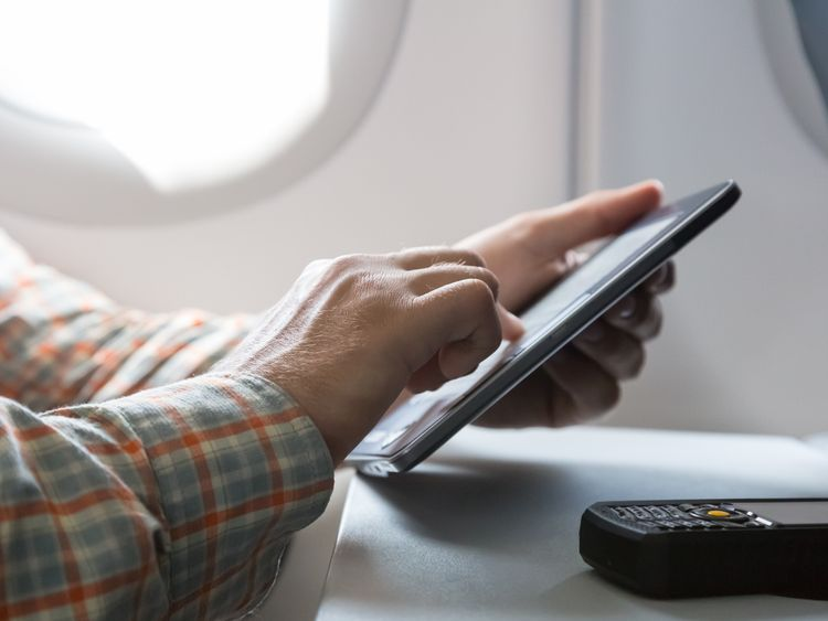 A man uses a tablet device on an airplane. File picture