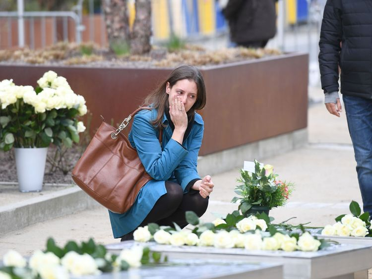 A woman pays her respects at a memorial to the victims