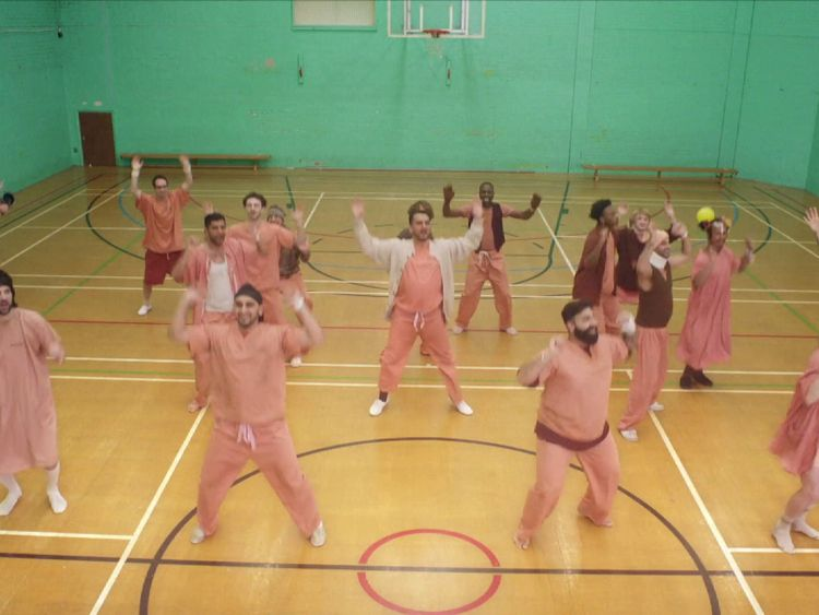 The band members and celebrities dance together in the gym