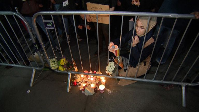 A woman wearing a headscarf lights a candle at one of the memorials set up at the vigil